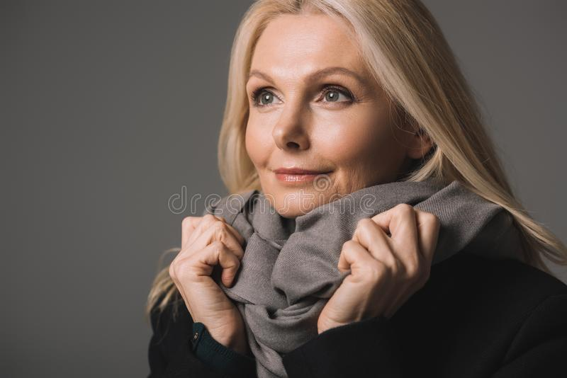 Beautiful mature woman in scarf and warm coat. Isolated on grey stock image
