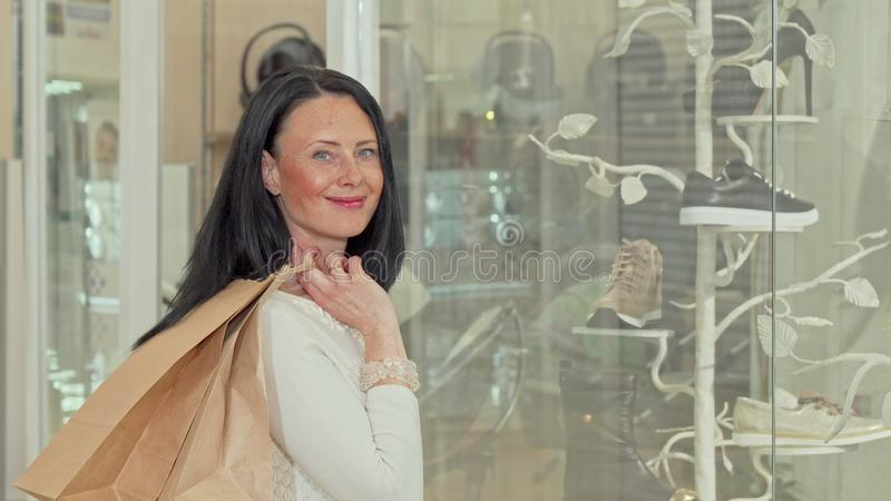 Beautiful mature woman smiling to the camera, while examining display of a store royalty free stock images