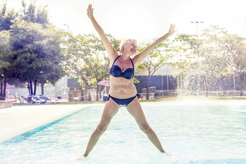 Beautiful mature woman in swimsuit makes gymnastics royalty free stock images