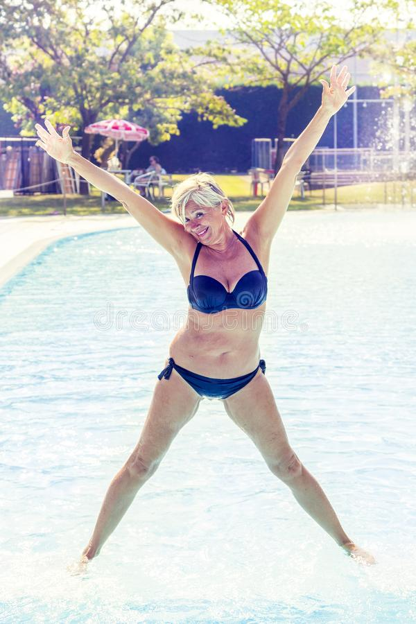 Beautiful mature woman in swimsuit makes gymnastics royalty free stock image