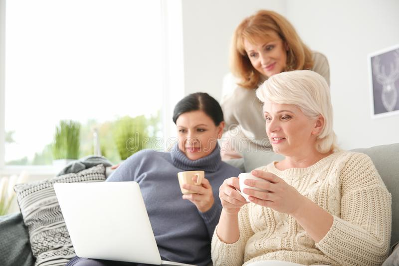Beautiful mature women drinking coffee while using laptop at home stock photos