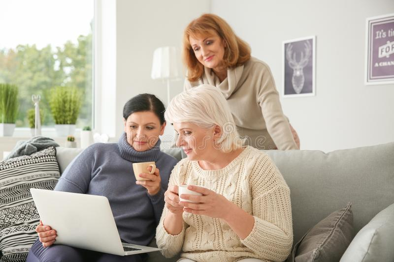 Beautiful mature women drinking coffee while using laptop at home royalty free stock photos
