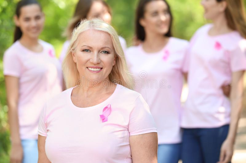 Beautiful mature woman with pink ribbon outdoors. Breast cancer concept. Beautiful mature women with pink ribbon outdoors. Breast cancer concept stock photography