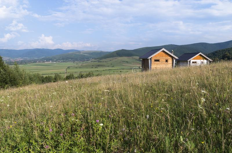 Beautiful meadows and hills with two small houses for spiritual royalty free stock images