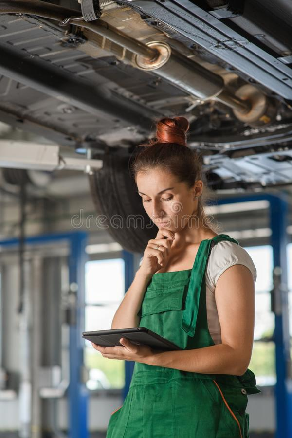 A beautiful mechanic girl reads technical documentation on a car. With a tablet royalty free stock photo