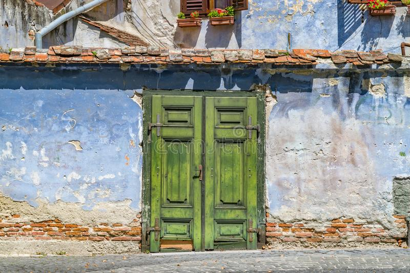 Beautiful medieval green door against a blue wall on a sunny summer day in Sibiu, Romania royalty free stock photography