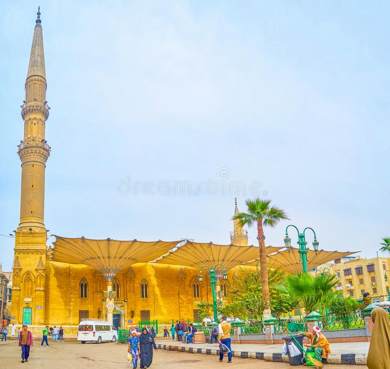 The beautiful medieval mosque in islamic Cairo, Egypt. CAIRO, EGYPT - DECEMBER 20, 2017: The old medieval Al-Hussein Mosque with tall minaret and huge umbrellas royalty free stock photography