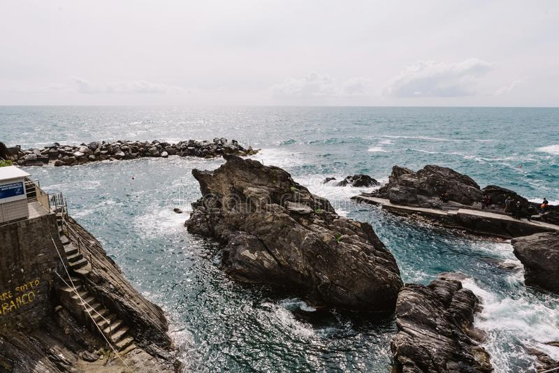 Beautiful Mediterranean sea water. Sea panorama and grey sky. Waves and seawater near large and formidable rocks royalty free stock photography