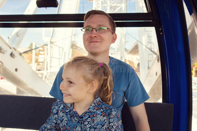 Beautiful men with his pretty happy daughter sitting in ferris w stock photo