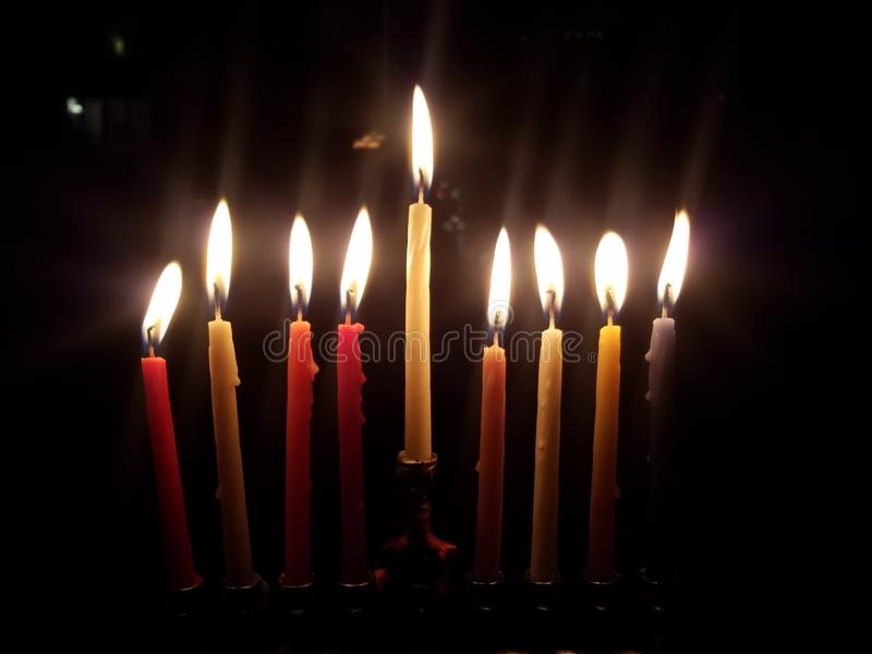 Beautiful menorah lit with candles on the last night of Chanukah. stock photos