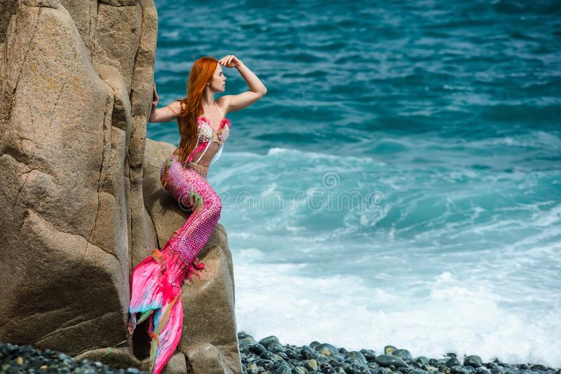 Beautiful mermaid on sea shore. Beautiful mermaid with long tail on sea shore stock images