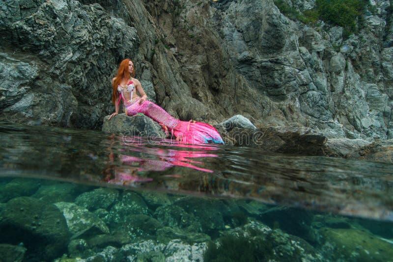Beautiful mermaid on sea shore stock photo