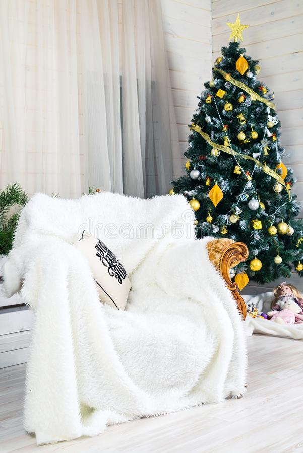 Beautiful Merry Christmas interior. Decorated Christmas tree, ar. Mchair with white warm blanket and white curtains. Concept of Merry Christmas and New Year royalty free stock photography