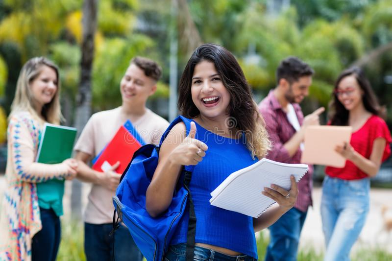Beautiful mexican female university student with group of students royalty free stock photos