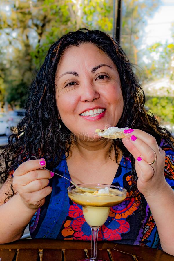 Beautiful Mexican woman savoring a delicious vanilla and caramel ice cream in a terrace of a cafeteria stock photography