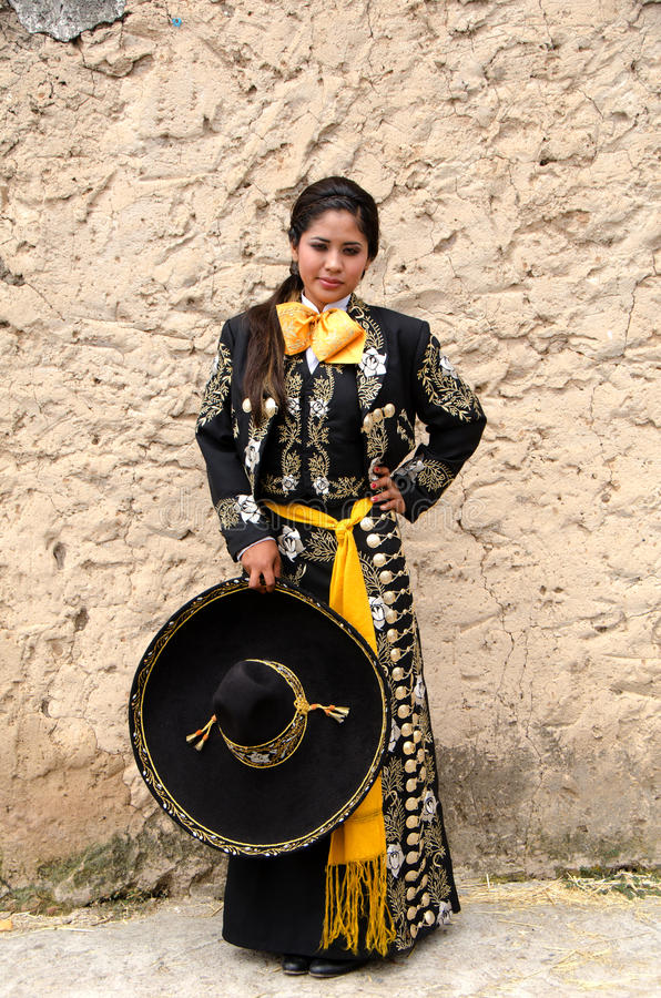 Beautiful Mexican woman in Traditional outfit. Young Mexican woman in traditional outfit with sombrero against stone wall royalty free stock images