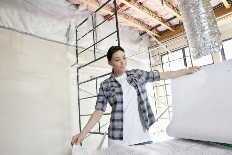 Download Beautiful Mid Adult Contractor Looking At Building Plans At Construction Site Stock Image - Image: 29672903