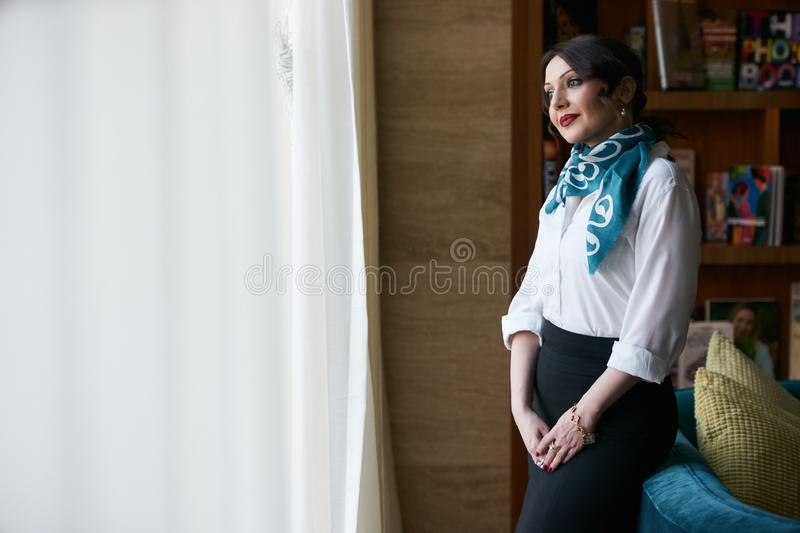 Beautiful middle age adult woman sitting on sofa, indoors stock photography