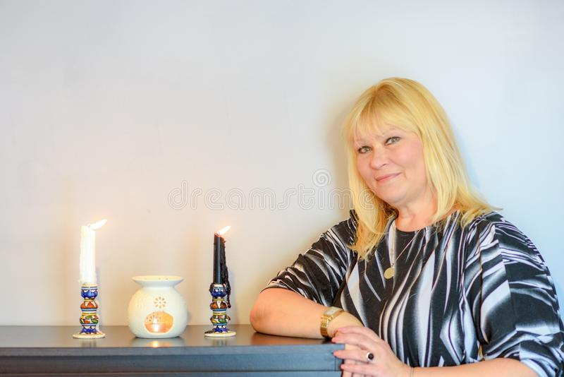 Portrait of beautiful middle age woman with candles. royalty free stock photo