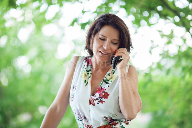 Beautiful middle age woman having a conversation on her mobile phone stock photography