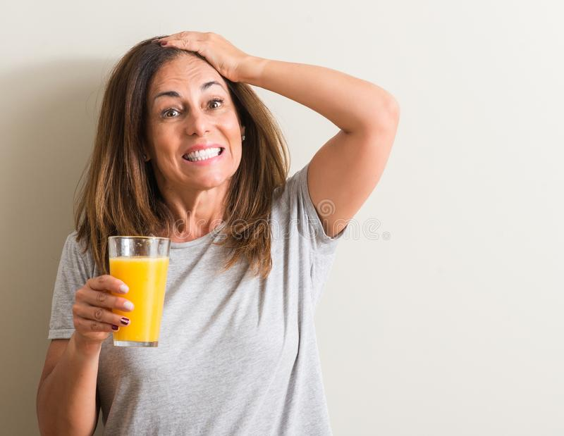 Beautiful middle age woman at home. Middle age woman drinking orange juice in a glass stressed with hand on head, shocked with shame and surprise face, angry and royalty free stock images