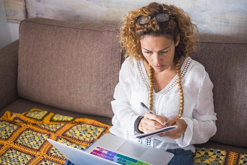 Beautiful middle age woman working at home woth a laptop while sitting on the sofa. taking notes and looking at the desktop of the royalty free stock images