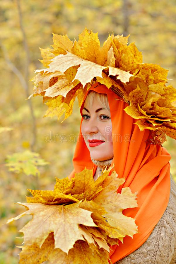 A beautiful middle-aged blonde girl in a wreath of yellow leaves in an orange scarf is standing in the forest, holding stock images