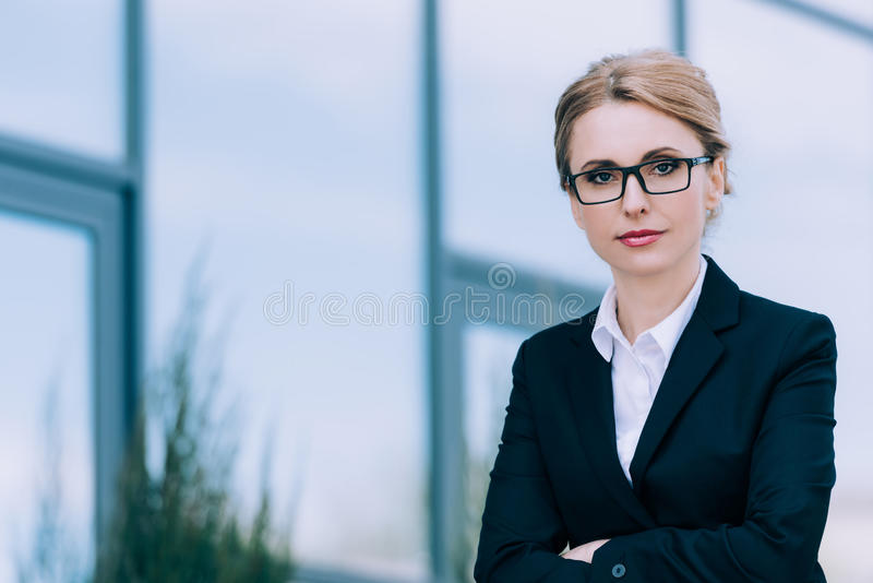 Beautiful middle aged businesswoman in eyeglasses standing with crossed arms and looking at camera stock photography
