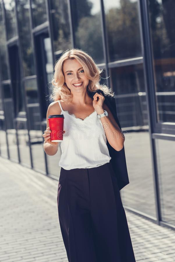 beautiful middle aged businesswoman holding paper cup and smiling royalty free stock photography