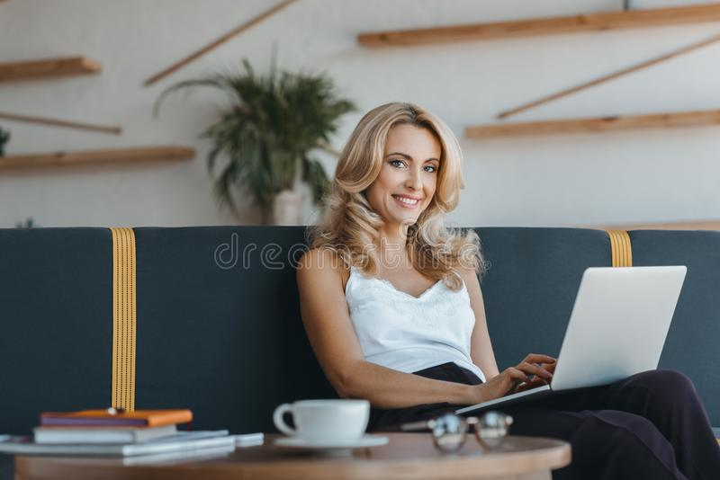 beautiful middle aged businesswoman using laptop and smiling at camera royalty free stock image