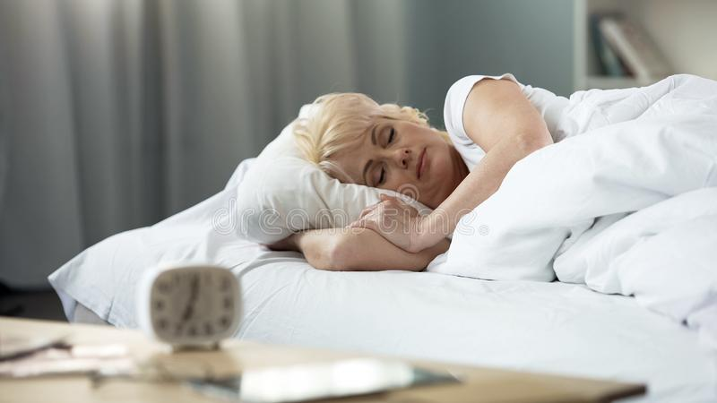 Beautiful middle-aged lady sleeping in bed, sleep cycle, peaceful rest, health. Stock photo stock photography