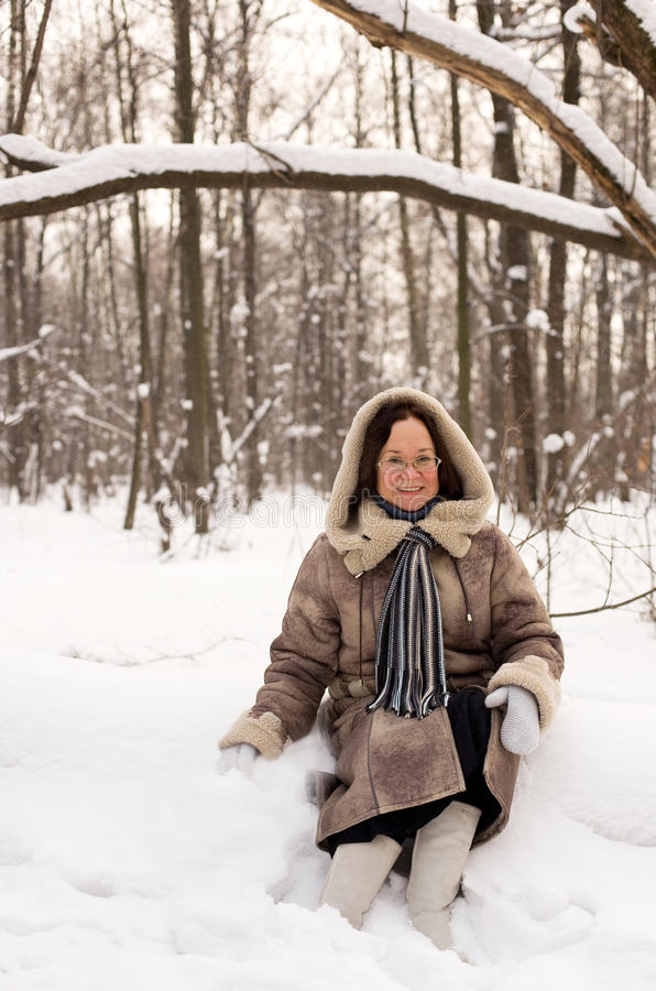 Beautiful middle aged winter forest. Beautiful middle aged woman sitting in snowbank at winter forest stock image