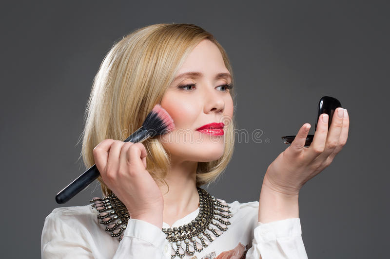 Beautiful middle aged woman applying blush. Beautiful middle aged blond woman applying blush over grey background. Copy space royalty free stock photography