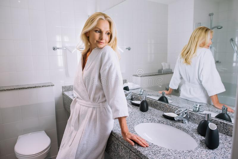 beautiful middle aged woman in bathrobe standing in bathroom stock images