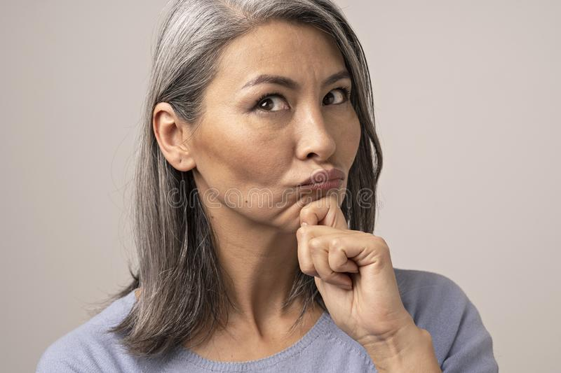 Beautiful mature woman blows lips while touching her chin stock photos
