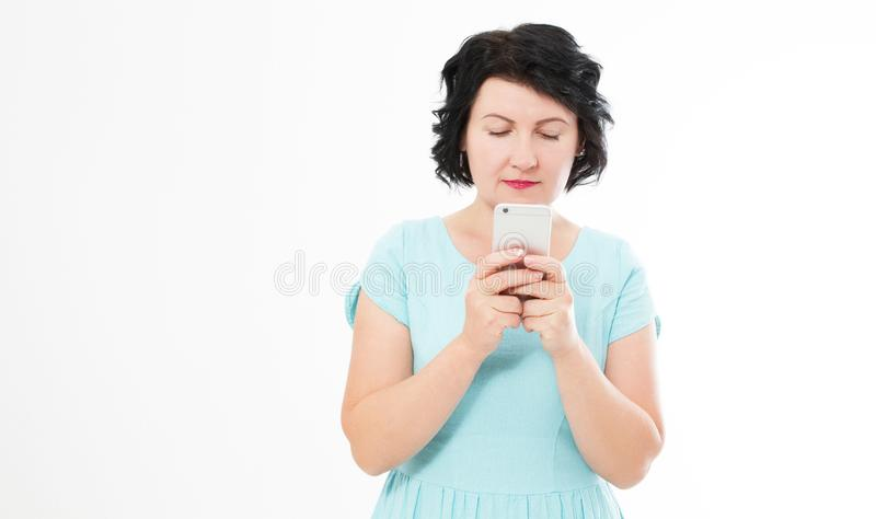 beautiful middle-aged woman in blue dress uses her phone. Charming brunette woman chatting on the internet royalty free stock photos