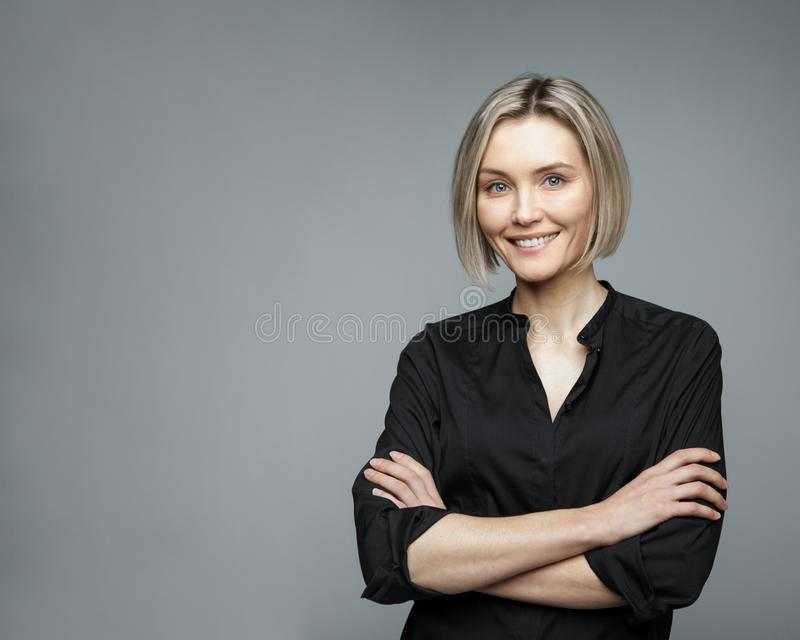 Beautiful middle-aged woman on a gray background in a black blouse smiling. stock photography