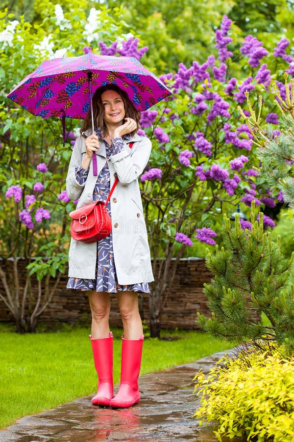 Beautiful middle aged woman in a light raincoat and with an umbrella stock photo