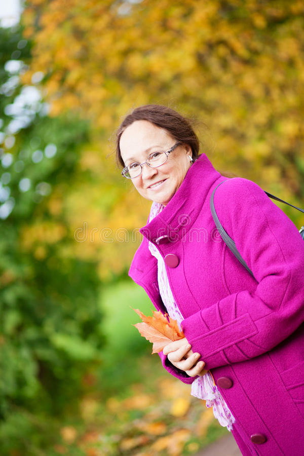 Beautiful middle aged woman in park. By fall royalty free stock photo