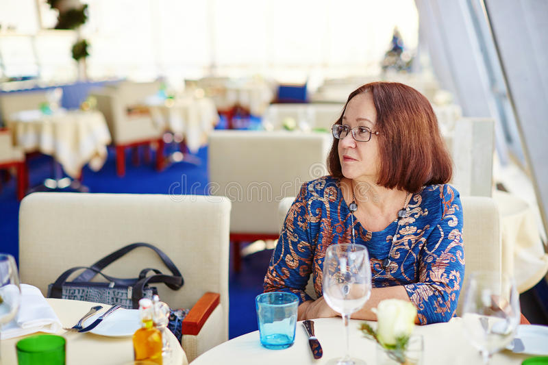 Beautiful middle aged woman in restaurant. Beautiful middle aged woman sitting at the table in restaurant stock images