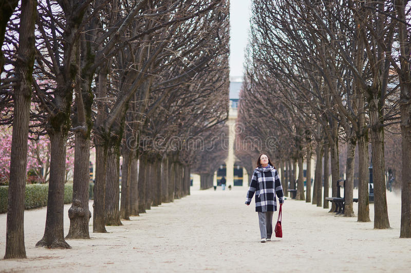 Beautiful middle aged woman walking in Parisian park. On a spring day royalty free stock photography