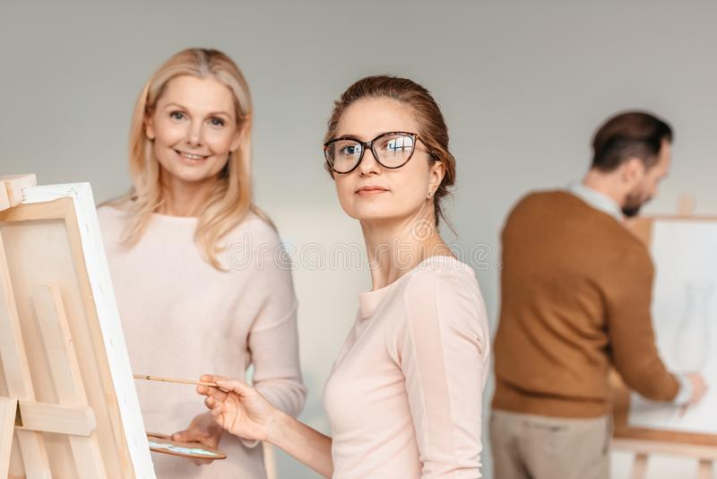 Beautiful middle aged women looking at camera while painting together. At art class royalty free stock images