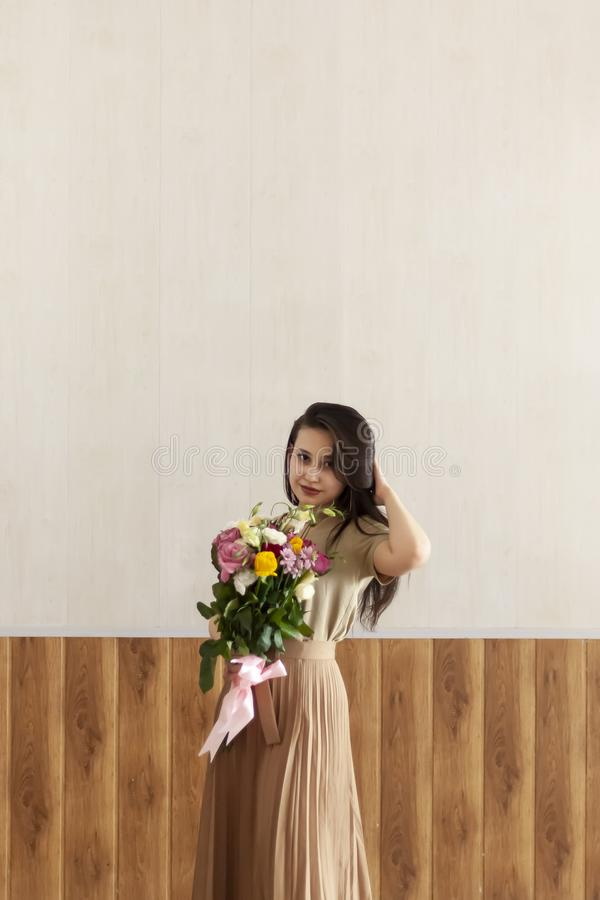 Beautiful middle-eastern girl with a bouquet of flowers in hands. Young attractive female with flowers. Portrait of charming,. Beautiful middle-eastern girl with stock images