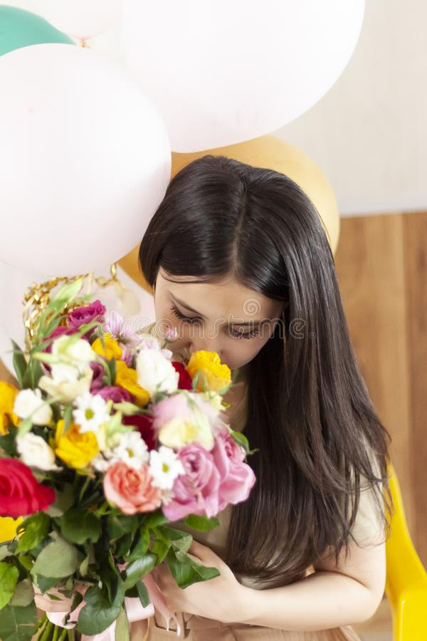 Beautiful middle-eastern girl with a bouquet of flowers in hands. Young attractive female with flowers. Portrait of charming,. Beautiful middle-eastern girl with royalty free stock images