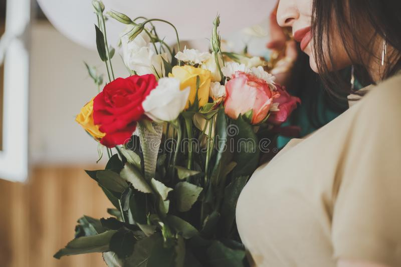 Beautiful middle-eastern girl with a bouquet of flowers in hands. Young attractive female with flowers. Portrait of charming, stock photos