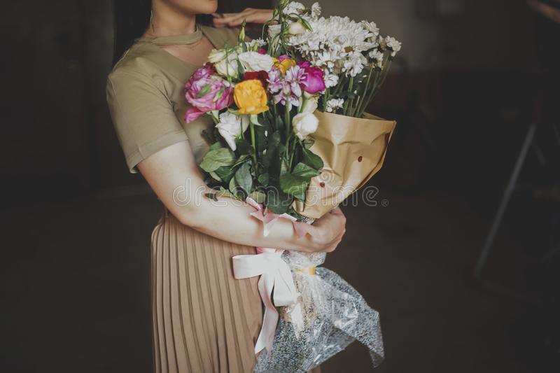 Beautiful middle-eastern girl with a bouquet of flowers in hands. Young attractive female with flowers. Portrait of charming,. Beautiful middle-eastern girl with royalty free stock image