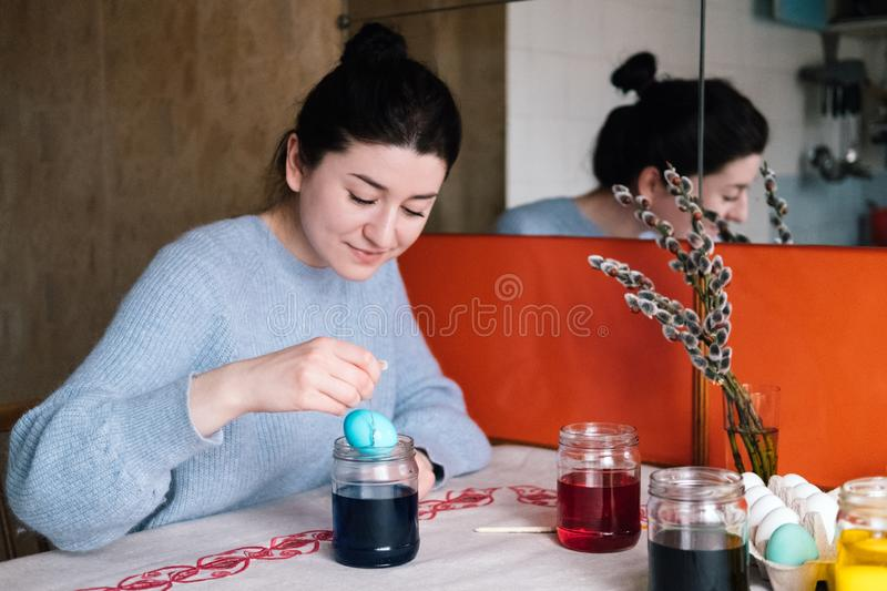 Beautiful millennial girl dyeing Easter eggs in jars royalty free stock photography