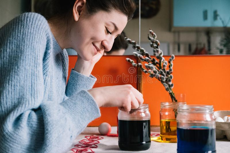 Beautiful millennial woman dying Easter eggs stock photos