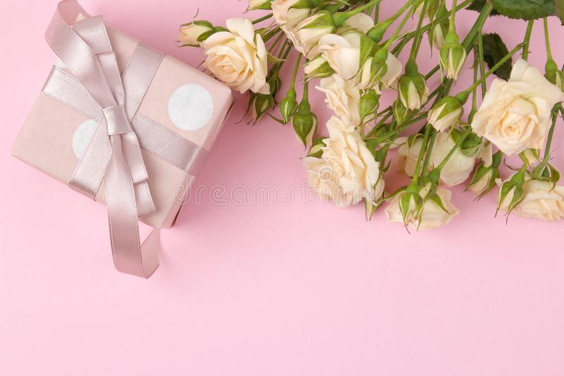 Beautiful mini roses with a pink gift box on a bright pink background. holidays. Valentine`s Day. women`s Day. top view. space f royalty free stock images