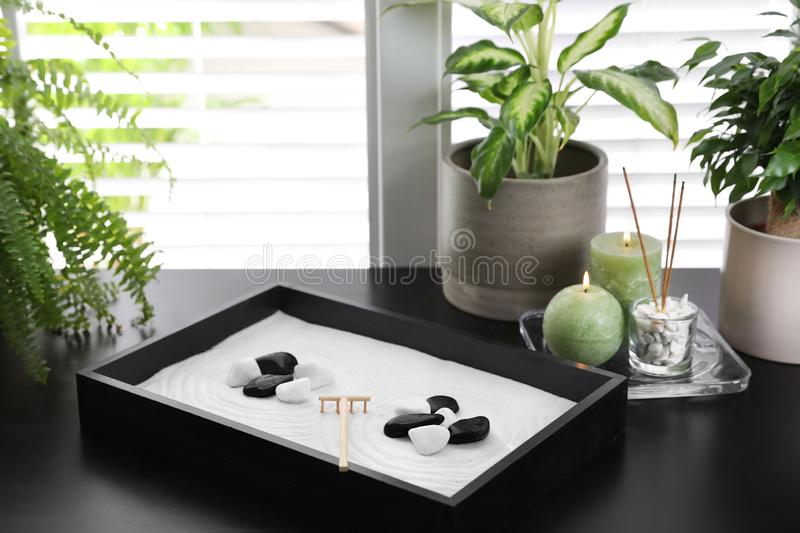 Beautiful miniature zen garden, candles and incense sticks on black table indoors stock image